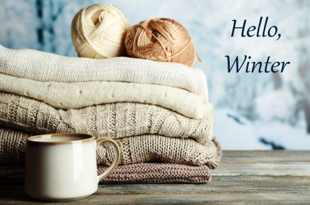 Cup of hot drink, knitting clothes and yarn on light winter background